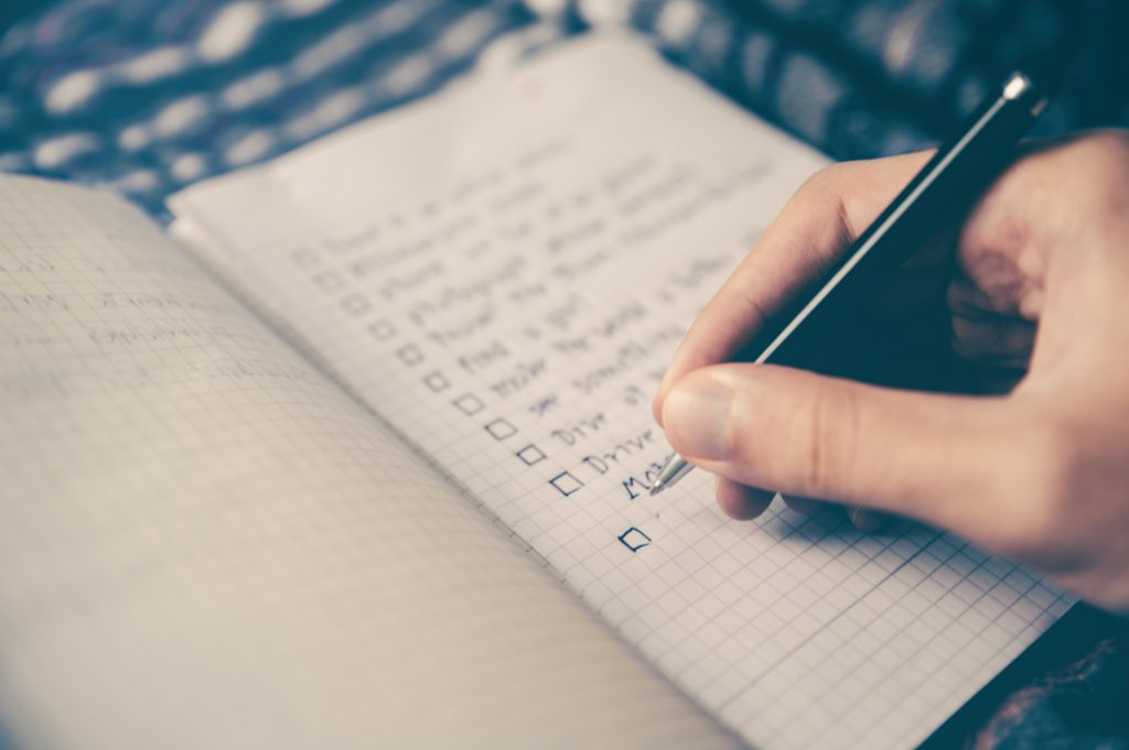 Person writing a checklist in notebook