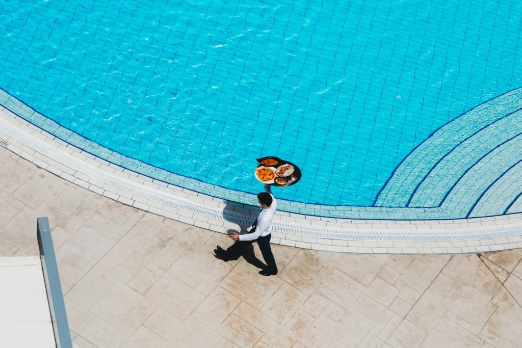 man carrying tray of food by pool