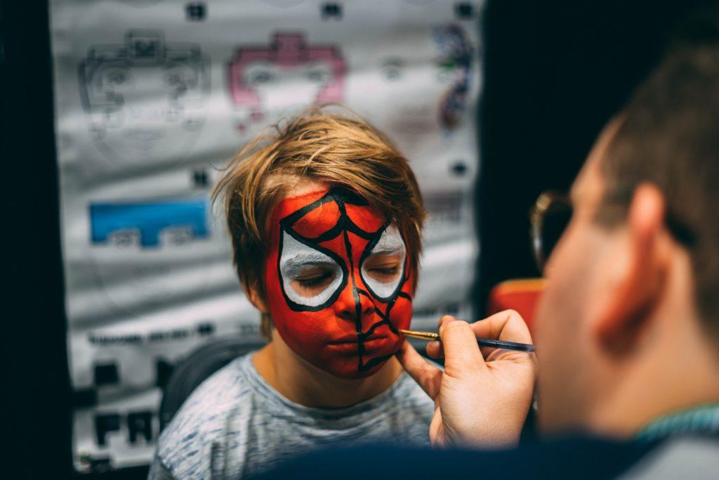 man painting boy's face