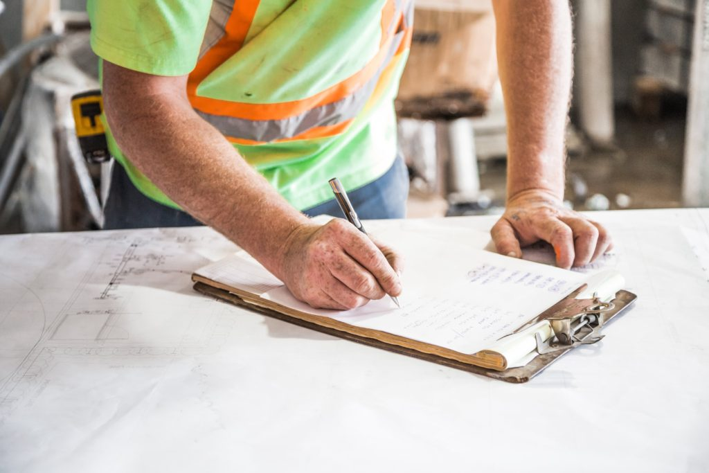contractor writing on clipboard