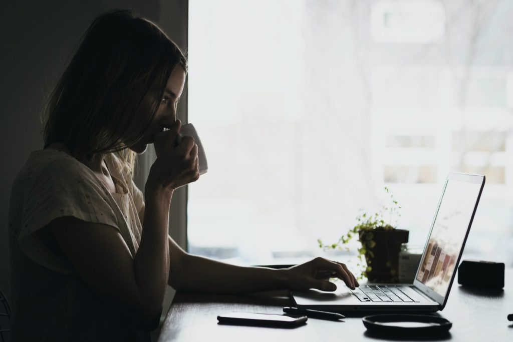 woman drinking coffee at home desk
