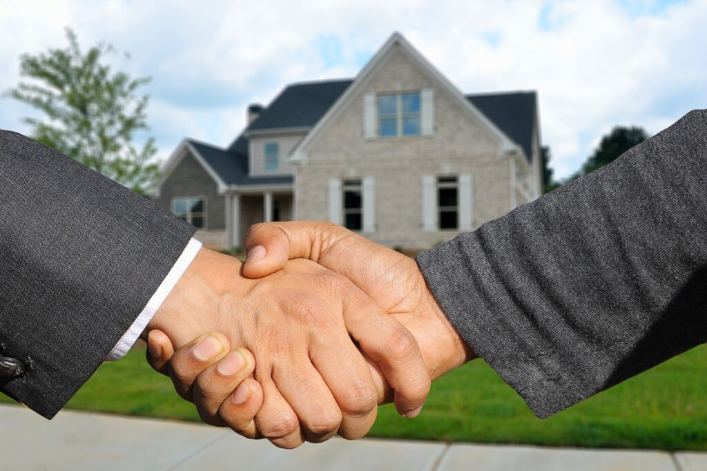 two men shaking hands in front of home