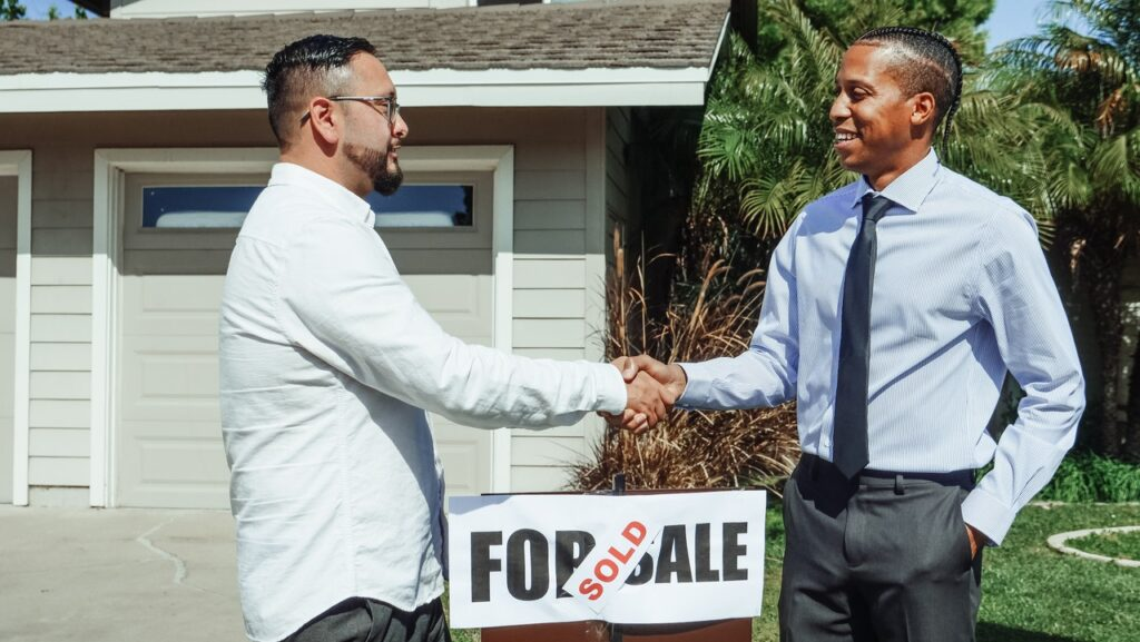 two man shaking hands in front of a home